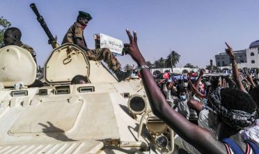 TOPSHOT - Sudanese protesters salute a military armoured vehicle as they gather during a demonstration in front of the military headquarters in the capital Khartoum on April 9, 2019. - Sudan's police on April 9 ordered its forces to avoid intervening against protesters as three Western nations threw their weight behind demonstrators' demands for a political transition plan in the country. (Photo by - / AFP)        (Photo credit should read -/AFP/Getty Images)