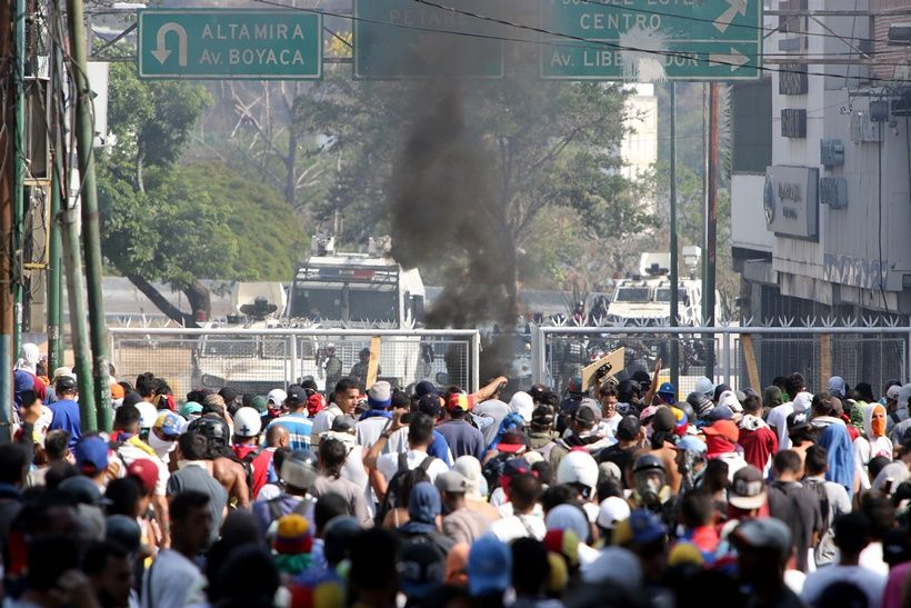 CARACAS, VENEZUELA - MAY 01: Venezuelan National Guard throw tear gas to Pro-Juan Guaidó demonstrators as they create a barricade in the street from a house's fence after the May 1 demonstration at Plaza Altamira on May 1, 2019 in Caracas, Venezuela. Yesterday, Venezuelan opposition leader Juan Guaidó, recognized by many members of the international community as the country's rightful interim ruler, urged an uprise to take Nicolas Maduro out of power. (Photo by Edilzon Gamez/Getty Images)