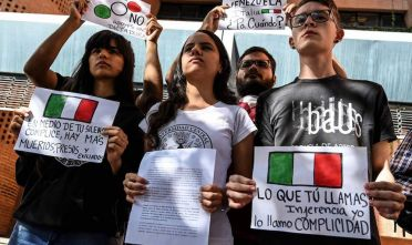 Students protest in front of the Italian embassy in Caracas in rejection to the position of the Italian government which blocked a European Union (EU) common declaration on Venezuela, on February 4, 2019. - Italy blocked a European Union (EU) common declaration on Venezuela on Monday, several diplomatic sources said in Brussels, after more than a dozen European countries have recognized opposition leader Juan Guaido as interim president of that country. (Photo by Juan BARRETO / AFP)        (Photo credit should read JUAN BARRETO/AFP/Getty Images)