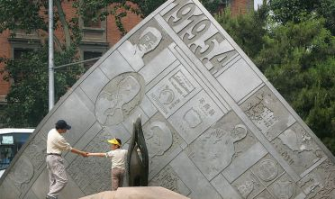 BEIJING, CHINA:  Holding hands, a father and child take a closer look at a young Mao Zedong on a sculpture dedicated to heroes of the 1919 May 4th Movement, 04 May 2005 in Beijing.  While China's present Communist leadership remains ever fearful of any kind of demonstrations, the significance of May 4th is that it was the first mass demonstration in modern Chinese history, sprung up by students after of signing of the Treaty of Versailles, in which a weak China had no say, which granted Shandong Province to Japan, sparking the movement against foreign dominance, especially Japanese, of China.  AFP PHOTO/Frederic J. BROWN  (Photo credit should read FREDERIC J. BROWN/AFP/Getty Images)