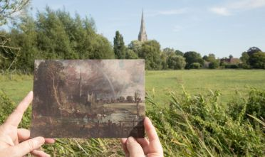 SALISBURY, ENGLAND - SEPTEMBER 14:  A postcard showing the image of  'Salisbury Cathedral from the Meadows' by John Constable which is being displayed as part of a new exhibition Constable in Context at Salisbury Cathedral is held up in front of the same view today on September 14, 2016 in Salisbury, England. The 1831 painting, part of the Tate's collection is touring the UK but its arrival in Salisbury will put Constable's painting in its historical and artistic context and is the highlight of the exhibition featuring images of Salisbury Cathedral through the ages.  (Photo by Matt Cardy/Getty Images)
