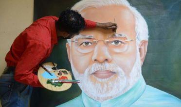 Il pittore Jagjot Singh Rubal dà gli ultimi ritocchi al ritratto del premier indiano Narendra Modi. Maggio 2019, foto di NARINDER NANU/AFP/Getty Images.