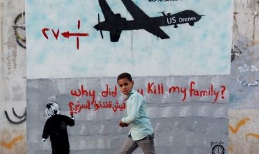 "A Yemeni boy (C) walks past a mural depicting a US drone and reading "" Why did you kill my family"" on December 13, 2013 in the capital Sanaa. A drone strike on a wedding convoy in Yemen killed 17 people, mostly civilians, medical and security sources said, adding grist to mounting criticism of the US drone war.  AFP PHOTO/ MOHAMMED HUWAIS        (Photo credit should read MOHAMMED HUWAIS/AFP/Getty Images)"