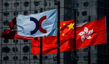 (L to R) The flags of the Hong Kong Stock Exchange (HKEX), China and Hong Kong are seen hoisted in Hong Kong on February 6, 2018. Hong Kong stocks were hammered almost five percent in the morning session on February 6, as global markets are routed after months of stellar gains and on worries about rising US interest rates. / AFP PHOTO / Anthony WALLACE        (Photo credit should read ANTHONY WALLACE/AFP/Getty Images)
