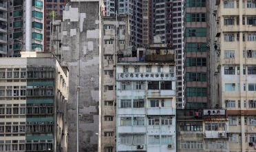 Modern apartments rise behind older buildings in the Sheung Wan district of Hong Kong on August 3, 2010. In February 2010, the government said prices of some luxury flats had returned to the peak levels of the 1997 property boom, partly thanks to deep-pocketed mainland Chinese buyers looking for safe investments. The wealthy financial hub is one of the world's most space-constricted cities, with even relatively well-off families often living in cramped quarters. AFP PHOTO / ED JONES (Photo credit should read Ed Jones/AFP/Getty Images)