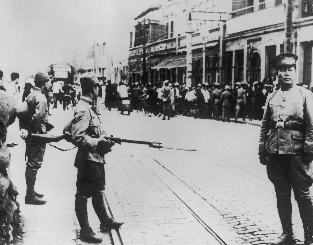 Truppe d'occupazione giapponesi (e un poliziotto cinese sulla destra) nei giorni successivi allo scoppio dell'incidente di Tianjin, luglio 1939 (Foto da: Keystone/Hulton Archive/Getty Images).