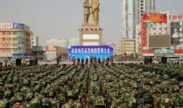 This file photo taken on February 27, 2017 shows Chinese military police attending an anti-terrorist oath-taking rally in Hotan, also known as Hetian, in northwest China's Xinjiang Uighur Autonomous Region. - On state television, the vocational education centre in China's far west looked like a modern school where happy students studied Mandarin, brushed up their job skills, and pursued hobbies such as sports and folk dance. But earlier this year, one of the local government departments in charge of such facilities in Xinjiang's Hotan prefecture made several purchases that had little to do with education: 2,768 police batons, 550 electric cattle prods, 1,367 pairs of handcuffs, and 2,792 cans of pepper spray. (Photo by STR / AFP) / China OUT        (Photo credit should read STR/AFP via Getty Images)