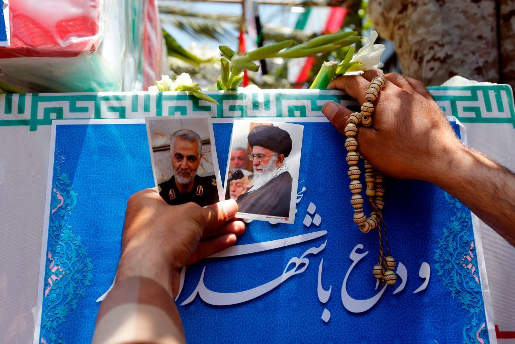An Iranian carries the portraits of Iran's Supreme Leader Ayatollah Ali Khamenei and Revolutionary Guard's Quds Force, Gen. Qassem Soleimani during the funeral of the victims of the attacks on Tehran's parliament complex and the shrine of revolutionary leader Ayatollah Ruhollah Khomeini, in the capital Tehran on June 9, 2017. - Tehran hit out at Washington and Riyadh as tens of thousands attended the funerals Friday for those slain in the first attacks in Iran claimed by the Islamic State group. (Photo by ATTA KENARE / AFP) (Photo by ATTA KENARE/AFP via Getty Images)