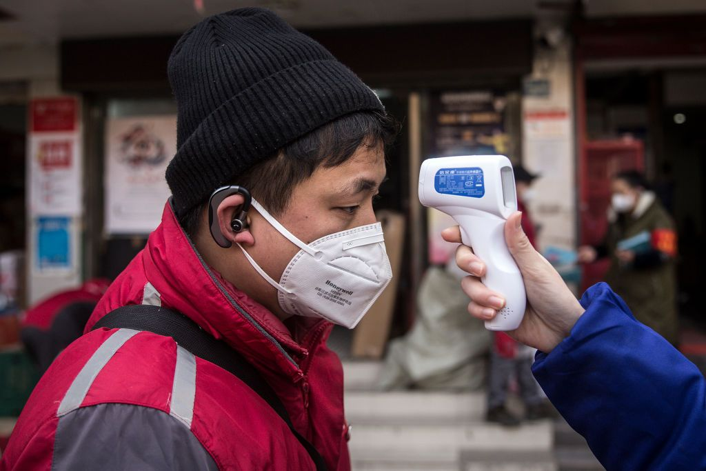 WUHAN, CHINA - JANUARY 29: (CHINA OUT)  A community worker checks the temperature of courier in an Express station on January 29, 2020 in Hubei Province, Wuhan, China. Due to a transit shut down and lack of supplies, couriers have became the city's suppliers. The 2019 coronavirus (2019-nCoV), which originated in Wuhan, China, has infected 6078 people and killed at least 132, mostly in China. (Photo by Getty Images)