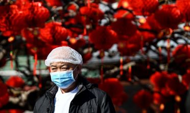 A man wearing a protective facemask walks along a street in Beijing on January 23, 2020. - China banned trains and planes from leaving the city of Wuhan at the centre of a virus outbreak on January 23, seeking to seal off its 11 million people to contain the contagious disease that has claimed 17 lives, infected hundreds and spread to other countries. (Photo by NOEL CELIS / AFP) (Photo by NOEL CELIS/AFP via Getty Images)