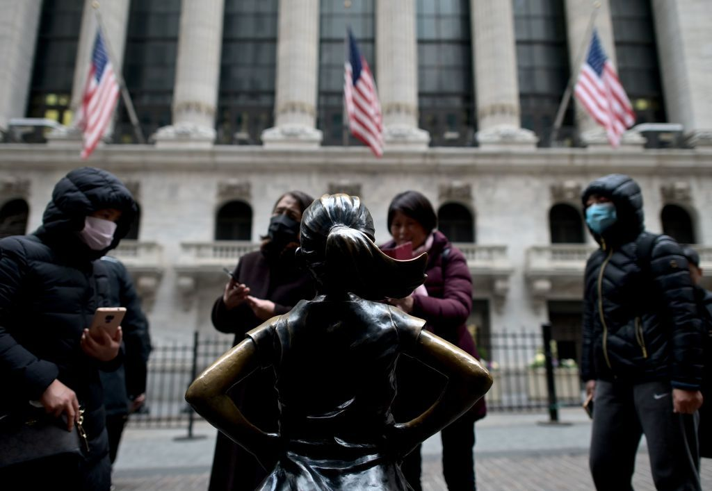 Chinese tourists with facial masks stand in front of the New York Stock Exchange (NYSE) on February 3, 2020 at Wall Street in New York City. - Wall Street stocks rose early Monday, bouncing after Friday's rout as markets monitored the coronavirus at the start of a week with key economic data and earnings reports. The Dow suffered the worst losses of the year on Friday as the death toll from the virus continued to climb and the ailment spread to additional countries. (Photo by Johannes EISELE / AFP) (Photo by JOHANNES EISELE/AFP via Getty Images)