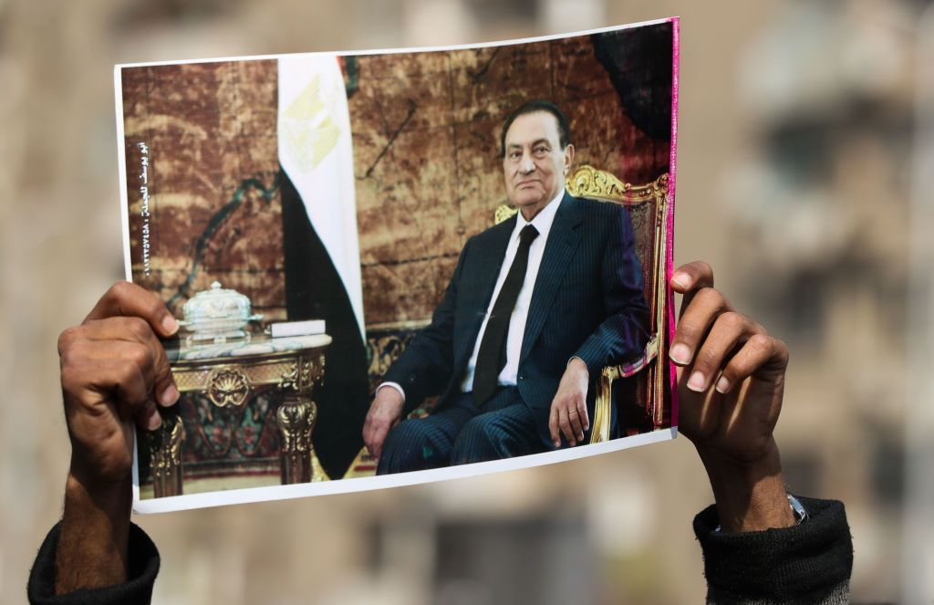 A supporter of Egypt's former president Hosni Mubarak lifts a picture of the late leader near the family cemetary where he will be buried, in the Heliopolis neighbourhood in the capital Cairo, on February 26, 2020. - Mubarak will be buried in a trendy Cairo suburb after a military funeral organised by the state to honour his war-time heroics. Mubarak, who died on February 25 aged 91 in a Cairo military hospital, crafted a lasting image of an autocrat in the region. (Photo by Mohamed el-Shahed / AFP) (Photo by MOHAMED EL-SHAHED/AFP via Getty Images)