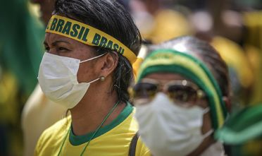 Demonstrators wear protective face masks during a gathering in support of Jair Bolsonaro, Brazil's president, outside of the National Congress in Brasilia, Brazil, on Sunday, March 15, 2020. Thousands of people gathered for anti-Congress protests on Sunday, even after President Bolsonaro suggested cancelling amid the growing coronavirus outbreak in the country. Photographer: Andre Coelho/Bloomberg via Getty Images