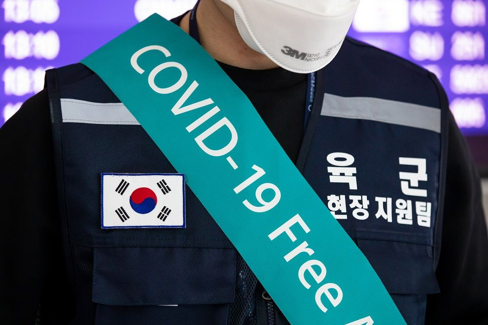 """A South Korean soldier wearing a banner reading """"Covid-19 Free"""" and a protective mask stands at a temperature screening point at Incheon International Airport in Incheon, South Korea, on Monday, March 9, 2020. The coronavirus outbreak in South Korea is showing signs of slowing as the rate of new daily infections falls and health authorities almost finished testing members of a religious sect at the center of the epidemic, the country's health minister said. Photographer: SeongJoon Cho/Bloomberg via Getty Images"""