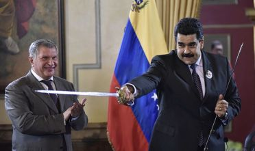 Bloomberg Best of the Year 2016: Nicolas Maduro, president of Venezuela, right, brandishes a sword given to him as a gift by Igor Sechin, chief executive officer of Rosneft PJSC, after Eulogio del Pino, president of Petroleos de Venezuela SA (PDVSA), not pictured, and Sechin signed natural gas deals in Caracas, Venezuela, on Thursday, July 28, 2016. The agreements included a deal for Rosneft to participate in the Mariscal Sucre natural gas project. Photographer: Carlos Becerra/Bloomberg via Getty Images