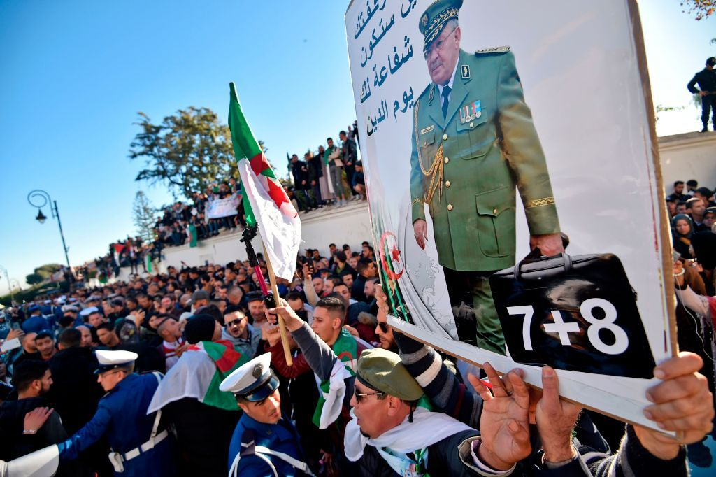 "People hold up a portrait of Algeria's late military chief Lieutenant general Ahmed Gaid Salah as they gather outside the ""Palais du Peuple"" (Palace of the People) during his funeral in Algiers on December 25, 2019. - Gaid Salah was seen as Algeria's de facto strongman following the April resignation of longtime president Abdelaziz Bouteflika in the face of mass demonstrations sparked by his bid for a fifth term. The army chief's body would be interred at the Al-Alia cemetary in western Algiers, the final resting place of other presidents and senior Algerian figures, the presidency had said. (Photo by RYAD KRAMDI / AFP) (Photo by RYAD KRAMDI/AFP via Getty Images)"