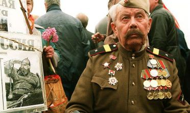 "MOSCOW, RUSSIA - MAY 9:  A veteran in uniform sits next to a box collecting  money for a pro-Soviet newspaper ""Sovietskaya Rossia"" during celebrations marking  Victory Day over Germany in WWII in Moscow 09 May 1994.  (Photo credit should read MICHAEL EVSTAFIEV/AFP via Getty Images)"
