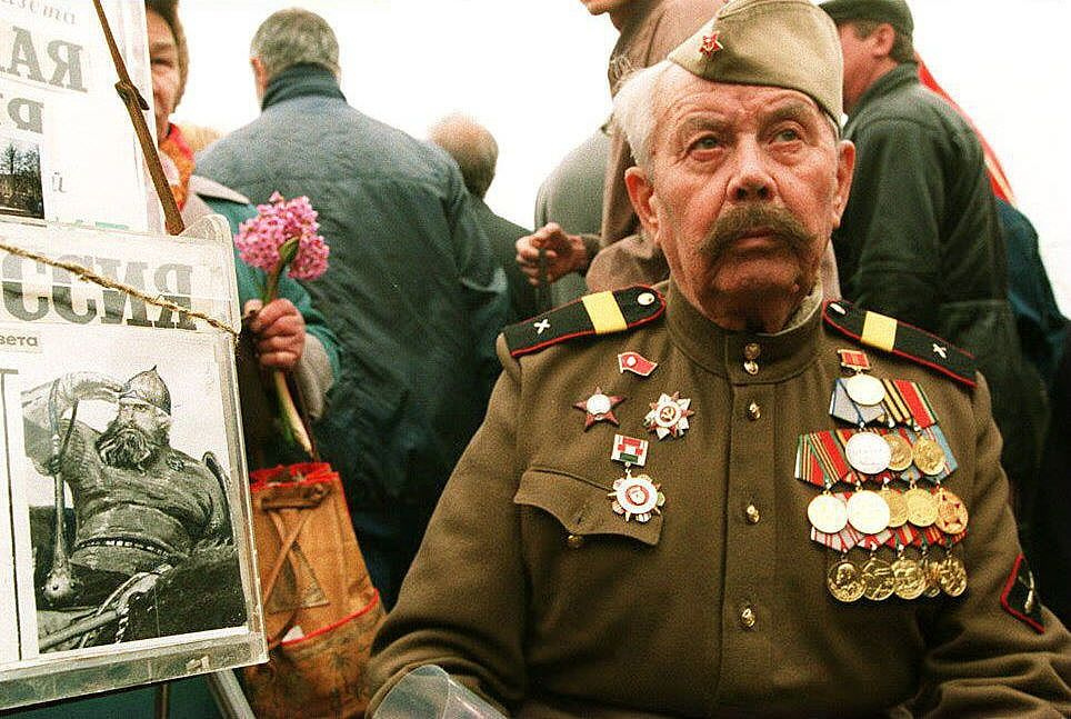 """MOSCOW, RUSSIA - MAY 9:  A veteran in uniform sits next to a box collecting  money for a pro-Soviet newspaper """"Sovietskaya Rossia"""" during celebrations marking  Victory Day over Germany in WWII in Moscow 09 May 1994.  (Photo credit should read MICHAEL EVSTAFIEV/AFP via Getty Images)"""