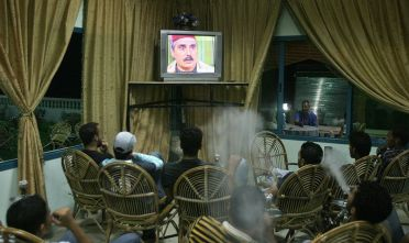 "TO GO WITH STORY BY MAGEDA AL-BATSCH Palestinians men blow smoke from their waterpipes as they watch the Syrian drama series ""Bab al-Hara (The Door to the Neighbourhood)"" in a cafe in Gaza City, 08 October 2007. The wildly popular turn-of-the-century serial has locals glued to their television screens nightly as they digest their Ramadan iftar, or meal that breaks their day-long fast. AFP PHOTO/MAHMUD HAMS (Photo credit should read MAHMUD HAMS/AFP via Getty Images)"