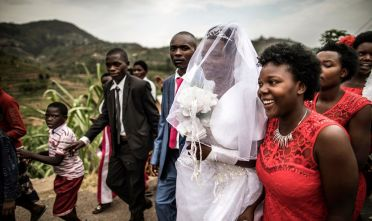 A wedding procession walks back from the ceremony on a road outside Ruhengeri, on August 1, 2017 in Rwanda. / AFP PHOTO / MARCO LONGARI        (Photo credit should read MARCO LONGARI/AFP via Getty Images)