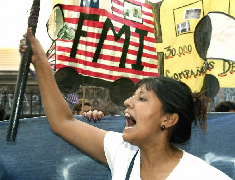 """BUENOS AIRES, ARGENTINA:  A member of the """"Movimiento de Trabajadores Desocupados"""" (unemployed people) shouts slogans against the International Monetary Fund, in front of the Argentinian Central Bank in Buenos Aires, 09 March 2004. Argentina faces a deadline on Tuesday to repay a loan of 3.1 billion dollars to the IMF and risked default by threatening not to pay despite attempts by the fund to keep debt talks on course for a solution. AFP PHOTO/Daniel GARCIA    (Photo credit should read DANIEL GARCIA/AFP via Getty Images)"""