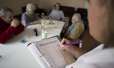 BERLIN, GERMANY - MARCH 18:  Doret Kohl (R) creates a directory in the geriatric day care facility of the German Red Cross (DRK, or Deutsches Rotes Kreuz) at Villa Albrecht on March 18, 2013 in Berlin, Germany.  A great number of senior Citzens struggle with various forms of dementia at Villa Albrecht.  The German Red Cross dates its origin back to 1863 with the founding of the Wuerttembergischer Sanitaetsverein, a medical association that provided care to wounded soldiers. Today the German Red Cross has four million members nationwide and is active in international aid and social care.  (Photo by Carsten Koall/Getty Images)