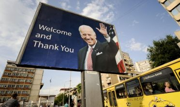 Kosovo Albanians walk past a billboard showing US Vice President Joe Biden in Pristina on May 19, 2009. Vice President Joe Biden began a landmark tour of the Balkans to demonstrate US engagement in the region and rebuild ties with Serbia after relations soured over Kosovo's independence last year. AFP PHOTO/ARMEND NIMANI (Photo credit should read Armend Nimani/AFP via Getty Images)