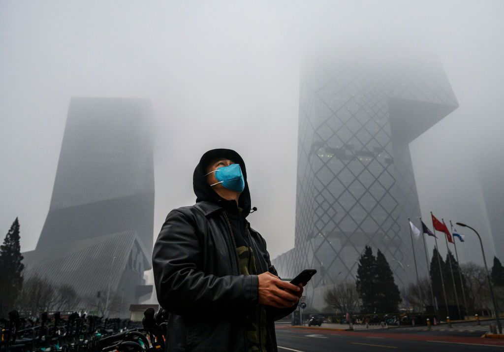 BEIJING, CHINA - FEBRUARY 13: A Chinese man wears a protective mask as he stands near the CCTV building in fog and pollution during rush hour in the central business district on February 13, 2020 in Beijing, China. The number of cases of the deadly new coronavirus COVID-19 rose to more than 52000 in mainland China Thursday, in what the World Health Organization (WHO) has declared a global public health emergency. China continued to lock down the city of Wuhan in an effort to contain the spread of the pneumonia-like disease which medicals experts have confirmed can be passed from human to human. In an unprecedented move, Chinese authorities have maintained and in some cases tightened the travel restrictions on the city which is the epicentre of the virus and also in municipalities in other parts of the country affecting tens of millions of people. The number of those who have died from the virus in China climbed to over 1300 on Thursday, mostly in Hubei province, and cases have been reported in other countries including the United States, Canada, Australia, Japan, South Korea, India, the United Kingdom, Germany, France and several others. The World Health Organization has warned all governments to be on alert and screening has been stepped up at airports around the world. Some countries, including the United States, have put restrictions on Chinese travellers entering and advised their citizens against travel to China. (Photo by Kevin Frayer/Getty Images)