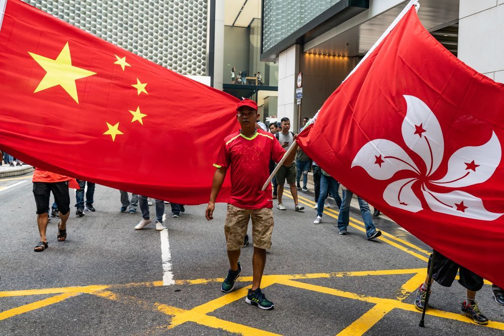 HONG KONG, CHINA - SEPTEMBER 18: Pro-China supporters wave Chinese and Hong Kong flags as they attempt to hold a march in a shopping mall but were met with large numbers of pro-democracy supporters on September 18, 2019 in Hong Kong, China. Pro-democracy protesters have continued demonstrations across Hong Kong, calling for the city's Chief Executive Carrie Lam to immediately meet the rest of their demands; including an independent inquiry into police brutality, the retraction of the word riot to describe the rallies, and genuine universal suffrage as the territory faces a leadership crisis. (Photo by Anthony Kwan/Getty Images)