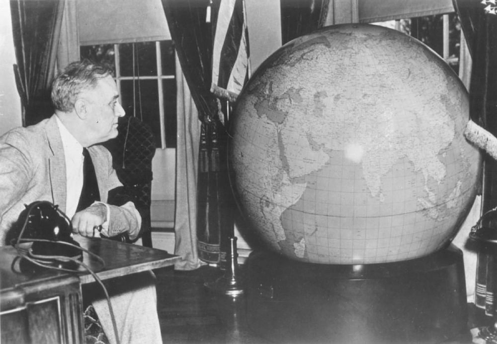 Franklin Delano Roosevelt nello Studio Ovale intento a osservare il grande mappamondo realizzato nel 1942 da Arthur H. Robinson e dalla sua Divisione Cartografica dell'Office of Strategic Services (Oss).