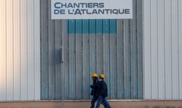 "Employees walk at the site of French ""Chantiers de l'Atlantique"" shipyard in Saint-Nazaire, on January 7, 2021. - The French ""Chantiers de l'Atlantique"" sale project to the Italian group Fincantieri is delayed by a month, announced the French governement on December 30, 2020. Italian shipbuilder Fincantieri is due to take majority control of the French shipyard STX under an agreement thrashed out between Paris and Rome to end a diplomatic row. (Photo by LOIC VENANCE / AFP) (Photo by LOIC VENANCE/AFP via Getty Images)"
