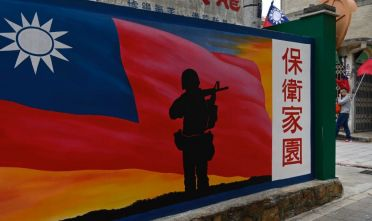 This photo taken on October 21, 2020 shows a tourist (R) walking past a mural painted on a wall on Taiwan's Kinmen islands, which lie just 3.2 kms (two miles) from the mainland China coast (in background) in the Taiwan Strait. - The tank traps on the beaches of Kinmen Island are a stark reminder that Taiwan lives under the constant threat of a Chinese invasion -- and fears of a conflict breaking out are now at their highest in decades. (Photo by Sam Yeh / AFP) / TO GO WITH Taiwan-China-US-politics-military-Kinmen,FOCUS by Amber WANG and Jerome TAYLOR (Photo by SAM YEH/AFP via Getty Images)