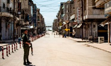 A member of the Kurdish internal security forces stands in the middle of an empty road in the city of Qamishli in Syria's northeastern Hasakeh province, on April 18, 2020, a day after local authorities of the Kurdish-dominated northern part of war-torn Syria recorded its first death due to the novel coronavirus outbreak. (Photo by DELIL SOULEIMAN / AFP) (Photo by DELIL SOULEIMAN/AFP via Getty Images)