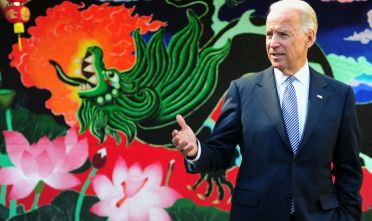 US Vice President Joe Biden gestures while speaking to the media after joining his visiting Chinese counterpart Xi Jingping to watch students perform a dragon dance at the International Studies Learning School in Southgate, outside of Los Angeles, on February 17, 2012. Xi's trip is the first to Los Angeles by a top-level Chinese leader for 13 years, and California sees it as an opportunity to strengthen Chinese investment in the western US state's major shipping, tourism and entertainment industries.     AFP PHOTO / Frederic J. BROWN (Photo by Frederic J. BROWN / AFP) (Photo by FREDERIC J. BROWN/AFP via Getty Images)