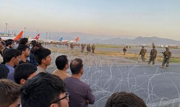 TOPSHOT - Afghans (L) crowd at the airport as US soldiers stand guard in Kabul on August 16, 2021. (Photo by Shakib Rahmani / AFP) (Photo by SHAKIB RAHMANI/AFP via Getty Images)