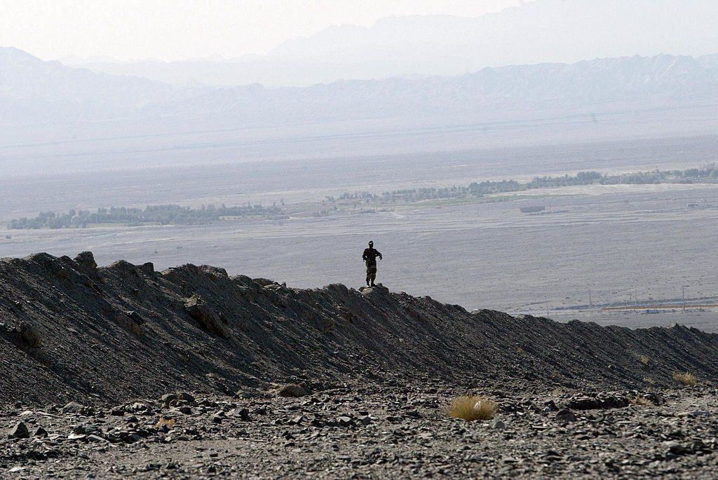 MIRJAVEH, IRAN:  An Iranian soldier stands guard on a mound built to prevent drug trafficking 02 December 2003 in the Mirjaveh point where the borders of Iran, Afghanistan and Pakistan meet. But despite the bulldozed trenches and mounds of dust and the string of machine-gun posts ought to be enough to put off all but the most suicidal drug traffickers hoping to enter Iran, officials taking the UN anti-drugs tsar on the tour admitted they were losing the war on drugs.     AFP PHOTO/Behrouz MEHRI   (Photo credit should read BEHROUZ MEHRI/AFP via Getty Images)