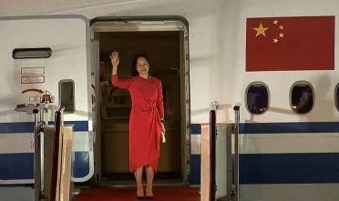 """This screen grab made from video released on September 25, 2021 by Chinese state broadcaster CCTV shows Huawei executive Meng Wanzhou waving as she steps out of the plane upon arrival following her release, in Shenzhen in China's southern Guangdong province. - - China OUT - XGTY / RESTRICTED TO EDITORIAL USE - MANDATORY CREDIT """"AFP PHOTO / CHINA CENTRAL TELEVISION (CCTV) """" - NO MARKETING NO ADVERTISING CAMPAIGNS (Photo by - / CCTV / AFP) / China OUT - XGTY / RESTRICTED TO EDITORIAL USE - MANDATORY CREDIT """"AFP PHOTO / CHINA CENTRAL TELEVISION (CCTV) """" - NO MARKETING NO ADVERTISING CAMPAIGNS / China OUT - XGTY / RESTRICTED TO EDITORIAL USE - MANDATORY CREDIT """"AFP PHOTO / CHINA CENTRAL TELEVISION (CCTV) """" - NO MARKETING NO ADVERTISING CAMPAIGNS (Photo by -/CCTV/AFP via Getty Images)"""