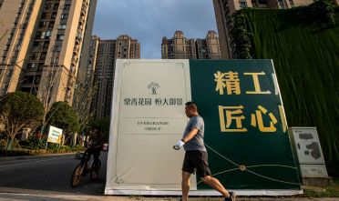 WUHAN, CHINA - SEPTEMBER 24: (CHINA OUT) A resident walks through the Evergrande changqing community on September 24, 2021 in Wuhan, Hubei Province, China. In 2015, Evergrande real estate acquired four super large projects in Haikou, Wuhan and Huizhou, with a total construction area of nearly 4 million square meters and a total amount of 13.5 billion yuan. Evergrande, China's largest property developer, is facing a liquidity crisis with total debts of around $300 billion. The problems faced by the company could impact China's economy, and the global economy at large.(Photo by Getty Images)
