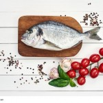 Fresh dorado fish on wooden cutting board with garlic, tomatoes, basil and peppercorns. Top view, copy space