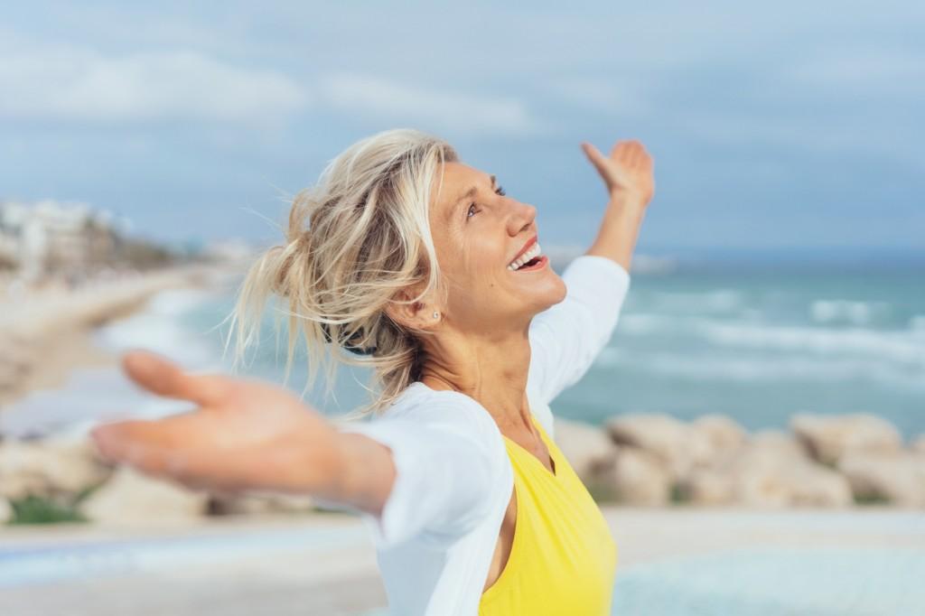 Joyful woman enjoying the freedom of the beach
