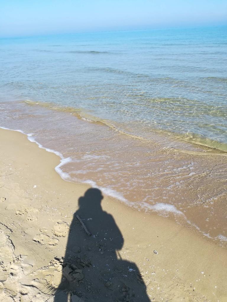 L'ombra di D. sulla spiaggia, un senso di pace che contrasta con la tempesta della mente