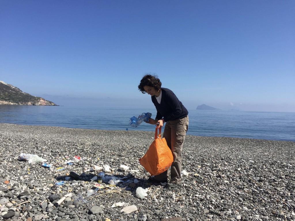 Adelaide alle prese con la plastica depositata dal mare su una  spiaggia delle Eolie