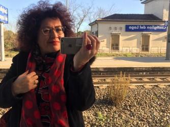 Giustina nella stazione di Castiglion del lago riflessa in una porta specchiata