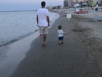 Mattia a passeggio con il suo papà sulla spiaggia