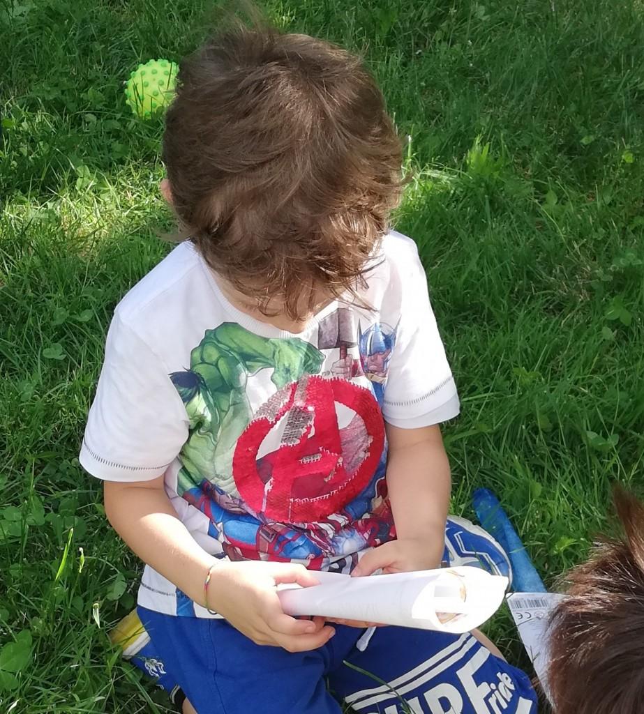 Michele al parco guarda il suo diploma durante la festa di fine anno