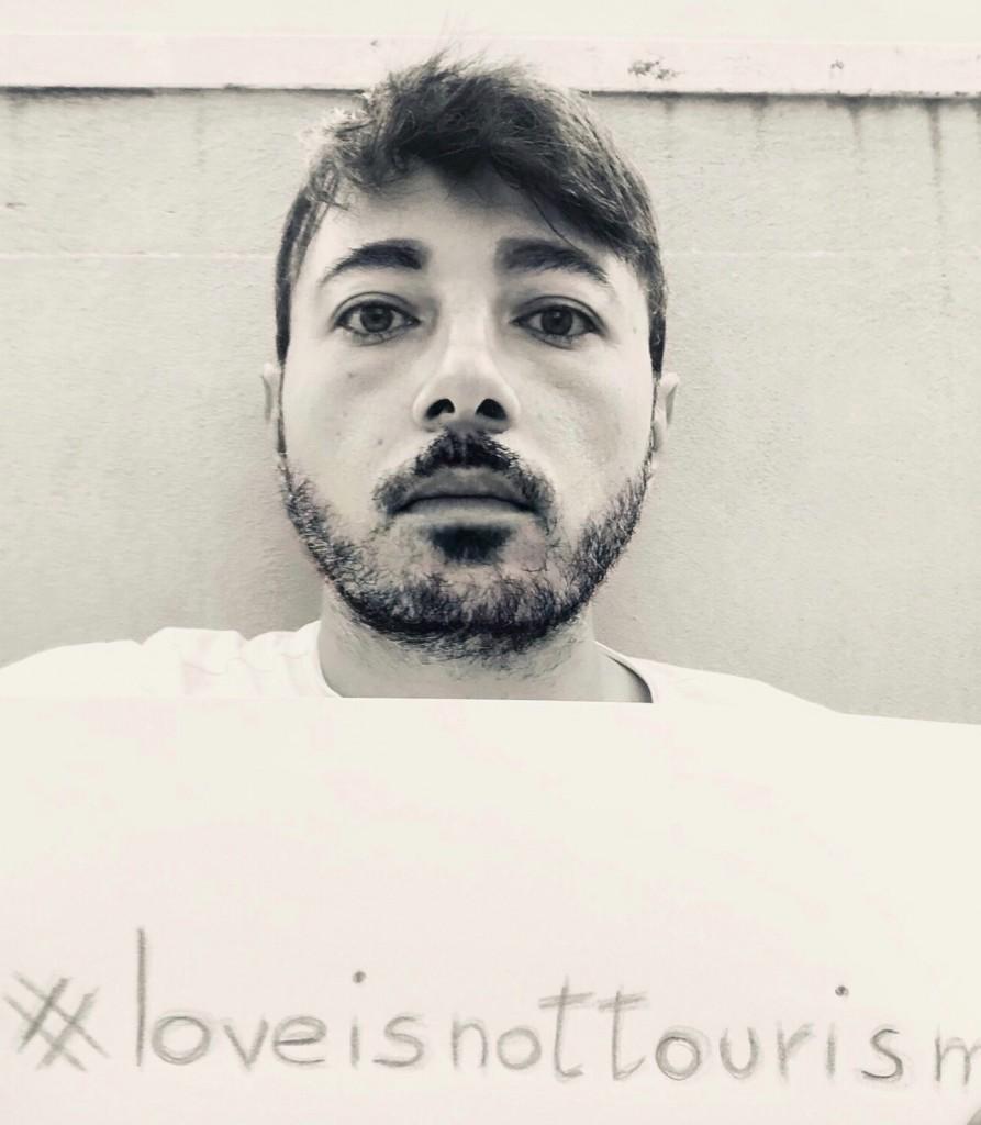 Luca con un cartello su cui è scritto l'hashtag della protesta #LoveIsNotTourism