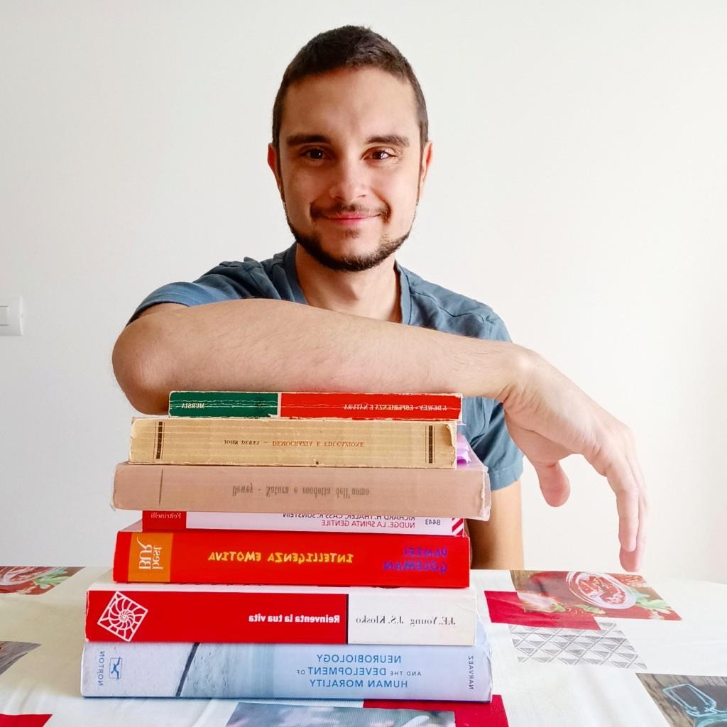 Giuseppe posa con una parte dei libri che ha studiato e che ora sembrano servirgli a poco