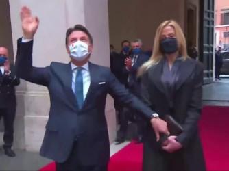 Conte, con la sua compagna nel cortile di Palazzo Chigi, risponde con un saluto all'applauso