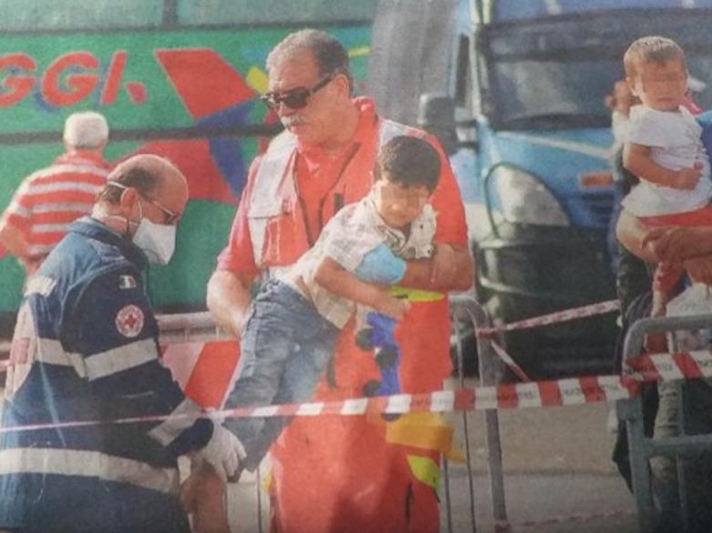 Battista con in collo un bambino migrante appena arrivato nel porto di Taranto