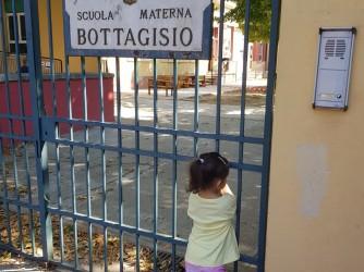Una foto simbolica, una piccola alunna della Bottagisio davanti al cancello chiuso